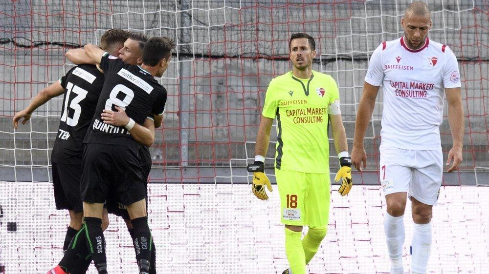 Kevin Fickentscher, et Pajtim Kasami sont dépités pendant que les joueurs du FC Saint-Gall exultent après l'ouverture de la marque.