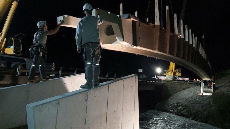 Une passerelle piétonne en bois de 40 mètres posée de nuit aux Trappistes