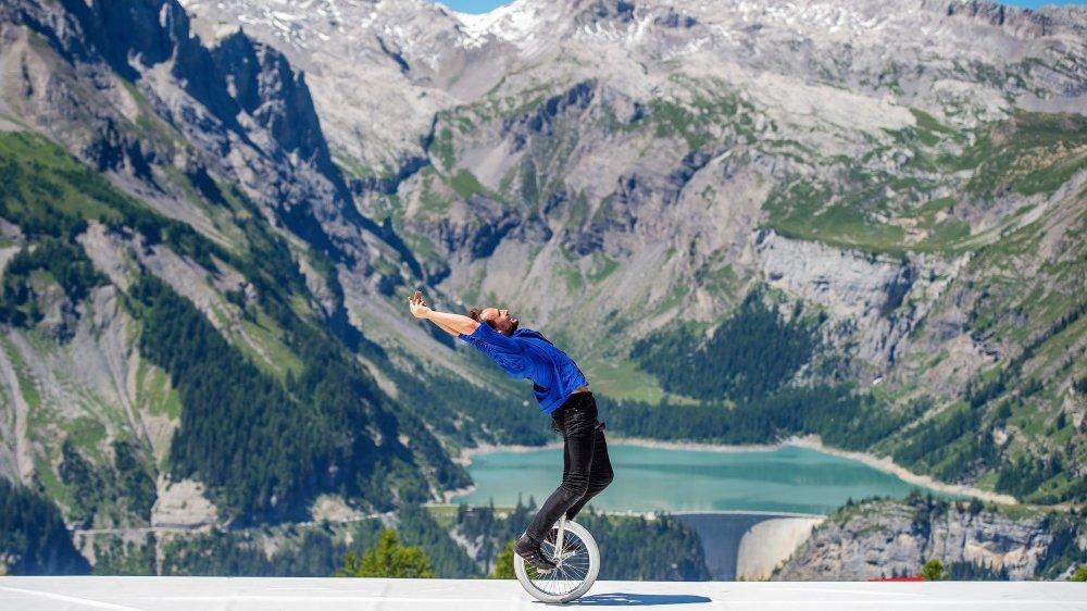 """Le spectacle """"Insaisissable"""" sur l'alpage, avec une vue imprenable sur le barrage de Zeuzier. Cirque au sommet offre une grande variété d'expériences cet été à Crans-Montana."""