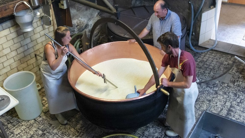 Martina et Frédéric s'apprêtent à fabriquer leur millième pièce de fromage à raclette au feu de bois sur l'alpage du Cœur sous le regard d'Eric Masseraz, le conseiller en économie laitière au canton du Valais.