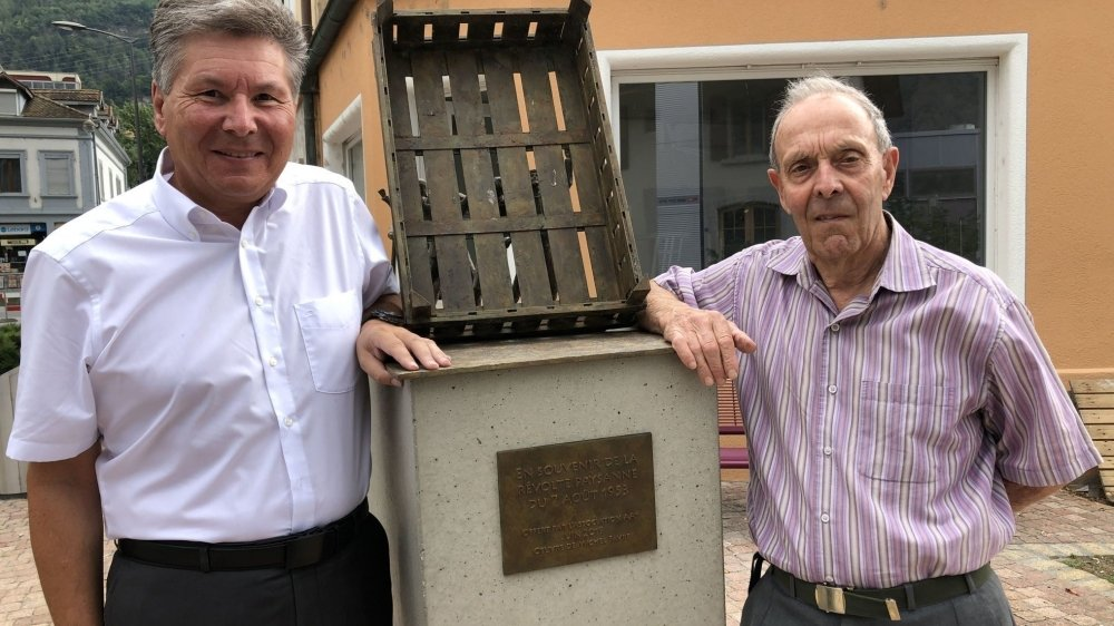 Le président de Saxon Christian Roth (à g.) et Marc Thomas, qui a participé aux événements de 1953, devant la sculpture de Michel Favre posée l'an dernier sur la place de la Révolte.