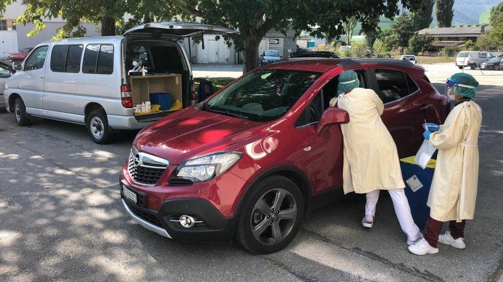 Deux assistantes médicales spécialement formées pour pratiquer les frottis nasopharyngés prennent en charge directement dans sa voiture un patient à proximité du théâtre des Halles à Sierre.